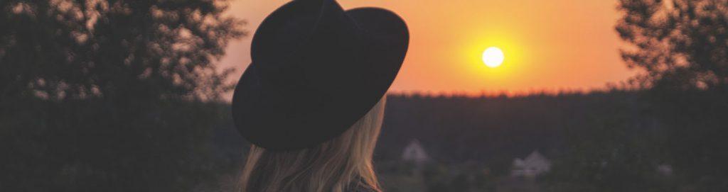 Ung kvinna i hatt som tittar mot horisonten