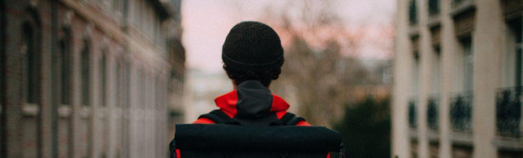 Kvinna sedd bakifrån som tittar ut över en gata