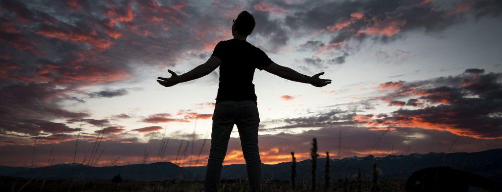 Ung man bakifrån med utsträckta händer som tittar på moln i solnedgång