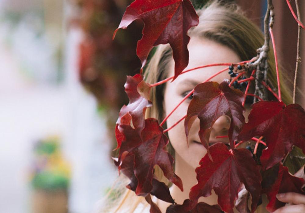 kvinna tittar mellan röda lönnlöv